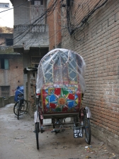 A colourful trishaw is parked in an alley.